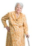 Old sad woman. Standing with a cane posing on a white background stock photo