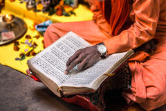 Old sadhu hand. Wearing hand watch pointing at line of holy book Varanasi, India Stock Photo