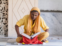 Old sadhu reading scriptures Stock Photography