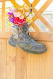 Old safety boot holding artificial flowers Stock Image