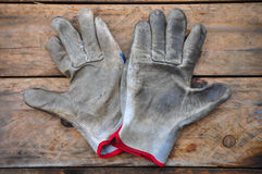 Old safety gloves on wooden background, Gloves on dirty works.  Stock Photos