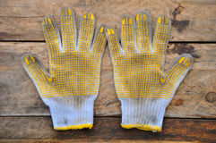 Old safety gloves on wooden background, Gloves on dirty works Royalty Free Stock Image