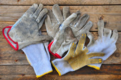 Old safety gloves on wooden background, Gloves on dirty works Stock Image