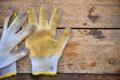 Old safety gloves on wooden background, Gloves on dirty works Stock Photos