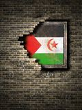 Old Sahrawi Arab Democratic Republic flag in brick wall. 3d rendering of a Sahrawi Arab Democratic Republic flag over a rusty metallic plate embedded on an old Royalty Free Stock Image