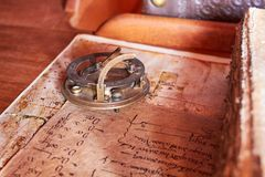 Old sailboat desk with an astrolabe. Old sailboat desk with and old book with aged paper stock image