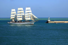 Old sailboat enters the port. On the background of a lighthouse Royalty Free Stock Photography