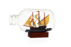 Old sailboat in glass bottle isolated over white background Royalty Free Stock Images