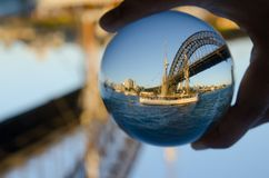 Old Sailboat at an ocean with Sydney Harbour bridge in the background photography in clear crystal glass ball. A beautiful Old Sailboat at an ocean with Sydney royalty free stock image