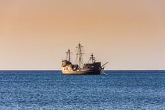 Old Sailboat sailing under a Caribbean sunset. Old wooden sailboat at sunset in the Caribbean sea. Beautiful sky color at twilight. Blue water. Side view stock photos