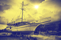 The Old sailboat. Old sailboat in the sun. Yellow and blue tinting royalty free stock image