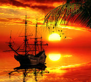 Old sailboat on a sunset skyline. Vintage retro classic old sailboat on a sunset skyline sky light background with palm tree on foreground. Travel, vacation Royalty Free Stock Photos