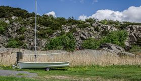 Old sailboat on wheels. Sailboat on wheels with grass and rocks in the background Stock Photos
