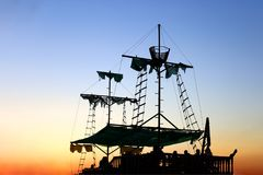 Old sailer pirate ship, with torn sails, at sunset. stock photography
