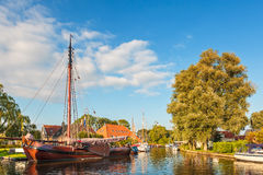 Old sailing boat in the Dutch village Heeg, Friesland. Old wooden sailing boat in a canal in the Dutch village Heeg, Friesland Stock Photo