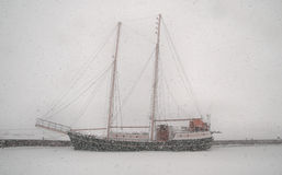 Old sailing boat in a heavy blizzard Stock Photos