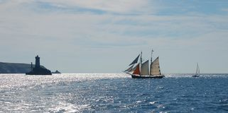 Old sailing boat near lighthouse Royalty Free Stock Photography