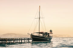 Old sailing boat at sunset. Old sailing boat in the harbor at sunset Stock Image