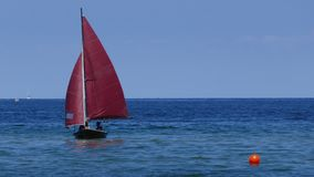 Small sailboat, an old sailing dinghy with dark red sails floats in the blue sea royalty free stock image