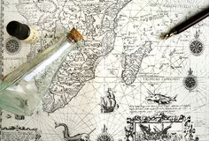 Old sailing map, pirate & hidden treasure concept. A photograph showing an antique sea chart, taken with a map inside a glass bottle, an antique manuscript pen royalty free stock photography