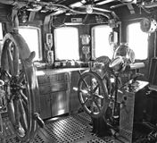 Old sailing ship commander deck. The commander deck of an old vessel with the steering wheels and polished brass nautical instruments royalty free stock images