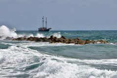 Old sailing ship in heavy seas. A old  sailboat moves through the water along a shoreline Royalty Free Stock Photos