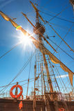 Old sailing ship mast. On blue sky background and sun rays Royalty Free Stock Image