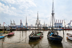 Old sailing ships in front of modern container terminals Stock Image