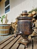 Old samovar on the background of firewood stock photo