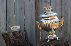 Old samovar on stump and bowl Stock Photos