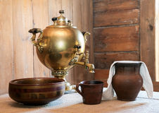 Old samovar and on a table in a country house Stock Images