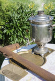 An old samovar was to boil on a table in the garden Royalty Free Stock Photo
