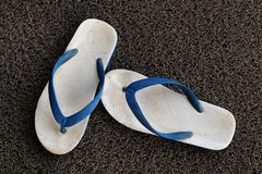 Old sandals on the grey carpet Royalty Free Stock Image