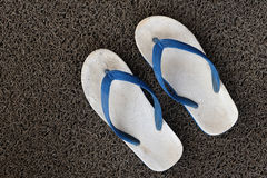 Old sandals on the grey carpet Royalty Free Stock Images