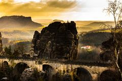 Old sandstone bridge in a german national park with an amazing v. You can see a sandstone bridge with some rocks in a beauriful orange sunset Royalty Free Stock Photography