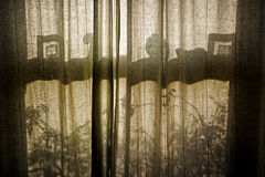 Old sash window through closed curtains. Old sash window silhouette through closed curtains Royalty Free Stock Images