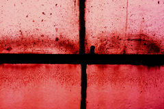 Old sash window frame against red. Dirty old sash window frame silhouetted against a red background Royalty Free Stock Image