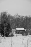 Old sawn log cabin in the snow in winter landscape bw Stock Photos