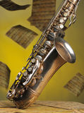 Old saxophone and flying musical notes on a backgr. Ound. The Musical instrument standing on notes with classical music of the beginning of 17 centuries Stock Images