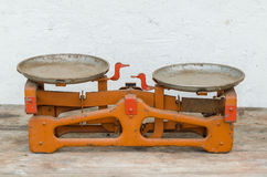 Old scale on the wooden table. Old orange scale on the wooden table Royalty Free Stock Photo