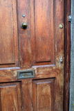 Old, scarred wood door of home, with brass letter slot. Old, scarred wood front door of rural country home, with brass letter slot cut out of panel stock photo