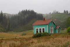Old school. Old wooden schoolbuilding in clouded countryside Stock Image