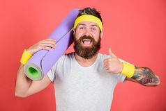 Old school aerobics concept. Subscribe flexibility challenge. Stretching and pilates concept. Athlete sport coach. Man. Bearded happy athlete hold mat red royalty free stock image