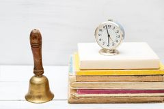 Old school bell and old clock on a pile of old books. Vintage. Object Stock Photo