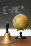 Old school bell on desk. In front of chalkboard Royalty Free Stock Image
