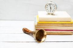 Old school bell and old clock on a pile of books. Education conc. Ept Royalty Free Stock Images