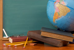 Old school books on a desk. With a globe in front of a green chalkboard Stock Image