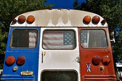 Bus converted into a patriotic camper. An old school bus decorated with the USA flag is converted into a patriotic red, white, and blue, camper Stock Photos