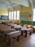 Old school: classroom with desks - v. Old school house classroom with desks at remote rural settlement, Matakohe, Northland, New Zealand - vertical format royalty free stock photos