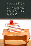 Old school desk with a stack of books Royalty Free Stock Images